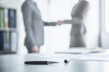 Two business people shaking hands in the background, pen lying on the table in the foreground