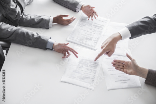 Four business people arguing and gesturing around a table during a business meeting, hands only