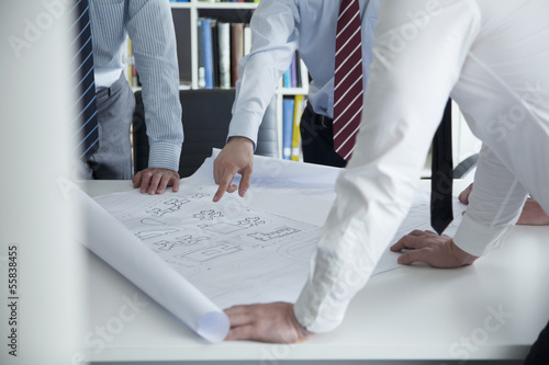 Two architects discussing over a blueprint in the office, mid section