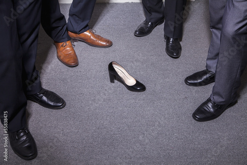 Businessmen standing in a circle around a woman's high heel, feet and legs only