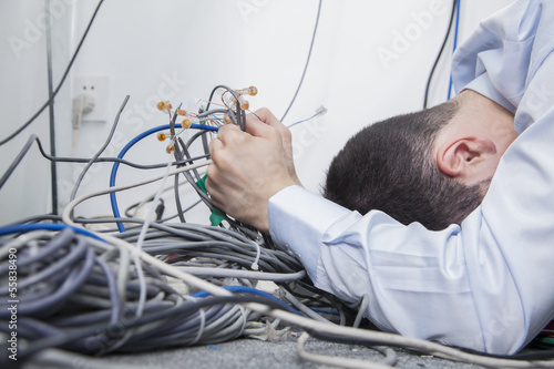 Frustrated man lying down trying to figure out and sort  computer cables
