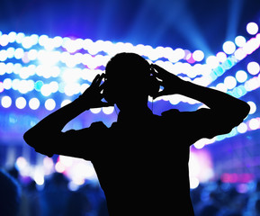 Silhouette of DJ wearing headphones and performing at a night club