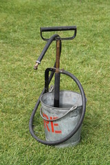 A Vintage Stirrup Pump in a Metal Fire Bucket.