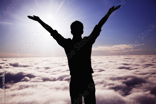 Silhouette of young man with arms raised with clouds and sky in the background