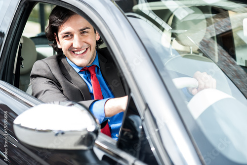Smart young businessman driving his new car
