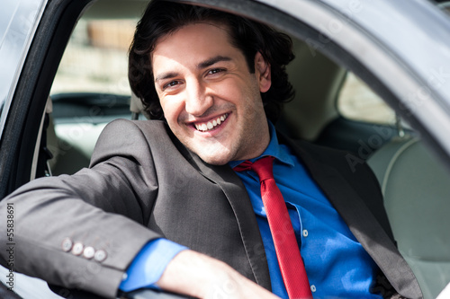 Portrait of handsome guy driving his car