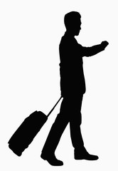 Silhouette of businessman checking wristwatch and pulling suitcase.