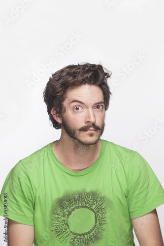 Young man with eyebrow raised looking at camera, studio shot