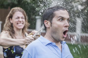 Couple playing with a garden hose and spraying each other outside in the garden, man has a shocked look, close-up