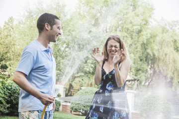 Couple playing with a garden hose and spraying each other outside in the garden