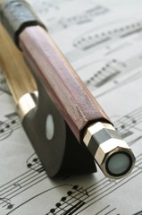 Violin bow end on sheet music background