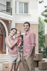 Portrait of smiling family in front of their new home
