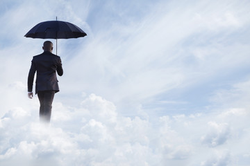 Businessman holding an umbrella and walking  away in dreamlike clouds