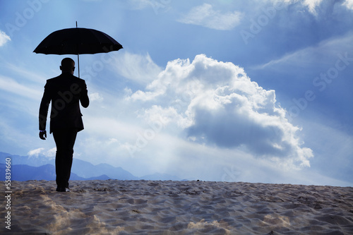 Businessman holding an umbrella and walking away in the middle of the desert with dreamlike clouds