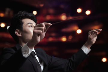 Young conductor with baton raised at a performance