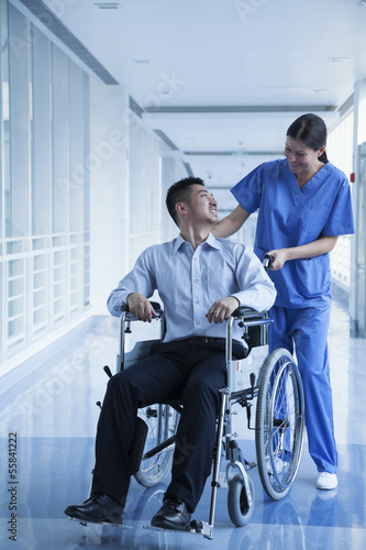 Smiling female nurse pushing and assisting patient in a wheelchair in the hospital