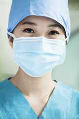 Portrait of young female surgeon wearing surgical mask in the operating room, close- up