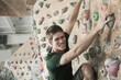Smiling young man climbing up a climbing wall in an indoor climbing gym