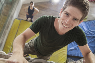 Close-up of smiling young man climbing up a climbing wall in an indoor climbing gym