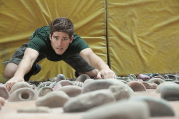 Determined young man climbing up a climbing wall in an indoor climbing gym, directly above