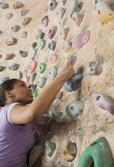 Determined young woman climbing up a climbing wall in an indoor climbing gym