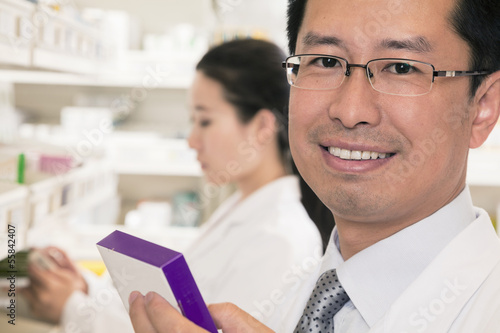 Portrait of smiling pharmacist holding prescription medication and looking at camera