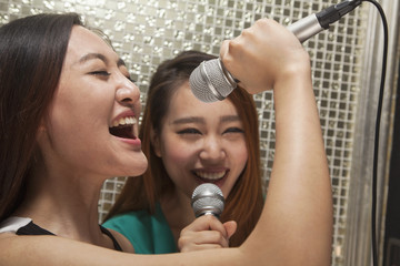 Two young female friends singing into a microphone at karaoke