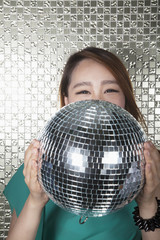 Young woman holding a disco ball, looking at camera in front of shiny wall
