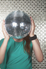Young woman holding a disco ball in front of her face