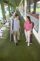 Young happy couple leaving the golf course with golf clubs and caddy