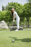 Young woman hitting the ball on the golf course