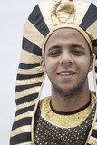 Portrait of smiling young man wearing a headdress from ancient Egypt, studio shot