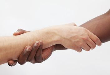 Two young men shaking hands, close-up, studio shot