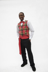 Portrait of young man in plaid vest and red bow tie, traditional clothing from Africa, studio shot