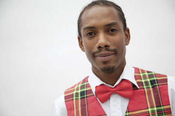 Portrait of young man in plaid vest and red bow tie, studio shot