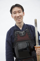 Portrait of young smiling man in traditional Japanese clothing holding a sword, studio shot