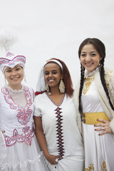 Portrait of three young multi-ethnic women in their traditional clothing, studio shot