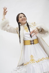 Portrait of young dancing woman with braids in traditional clothing from Kazakhstan, studio shot