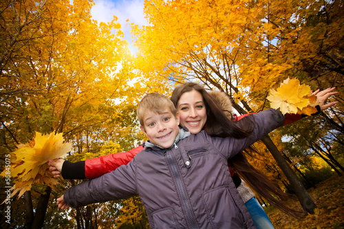 Mom and son are playing in a yellow autumn park