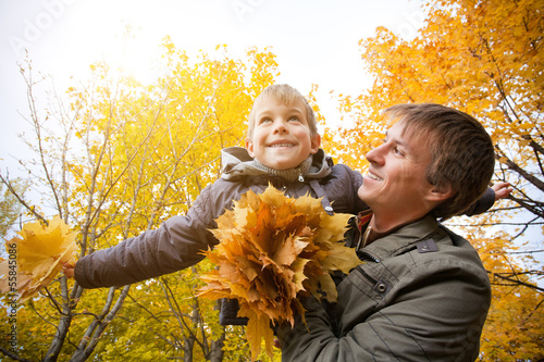 dad and son are playing in a yellow autumn park
