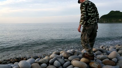Hiker sitting on the rocky shore and looks at sea