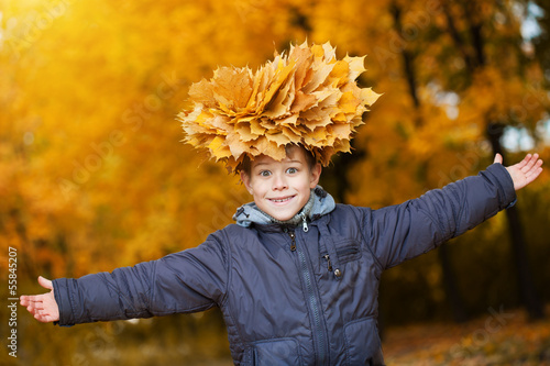 cheerful kid in a wreath on a autumn leafs background