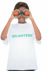 Cheerful volunteer woman looking through binoculars
