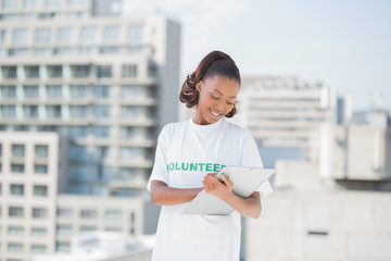 Smiling volunteer woman taking notes holding clipboard