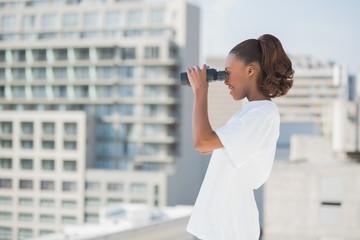 Side view of pretty woman using binoculars