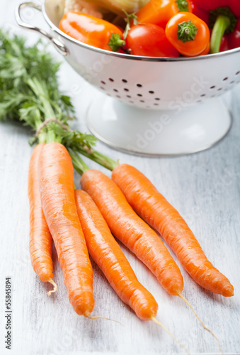 fresh carrot and vegetables in colander