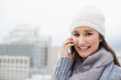 Smiling brunette with winter clothes on having a call