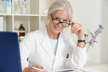 Ärztin blickt fragend über Brille.