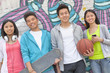 Portrait of four friends holding a skateboard and soccer ball hanging out in front of a wall covered in graffiti