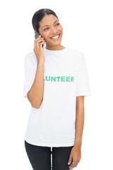Smiling model wearing volunteer tshirt having a phone call
